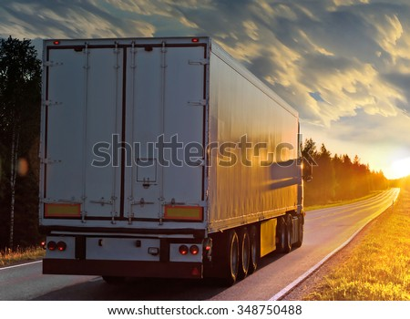 White truck on the rural road in evening. Sunset on the way.