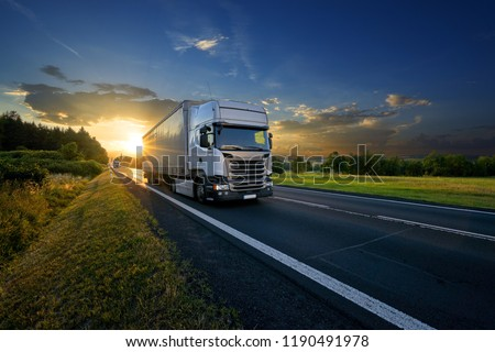 White trucks arriving on the asphalt road in rural landscape in the rays of the sunset