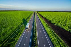 White trucks driving on asphalt road along the green fields in rural landscape. Road seen from the air. Aerial view landscape. shooting from a drone