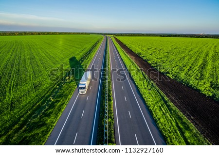 White trucks driving on asphalt road along the green fields in rural landscape. Road seen from the air. Aerial view landscape. shooting from a drone  #1132927160