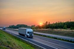 White trucks driving on the asphalt highway in the landscape at sunset