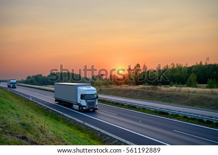 White trucks driving on the asphalt highway in the landscape at sunset