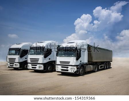 White trucks parked on a sand ground #154319366