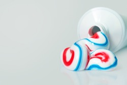 White tube with toothpaste isolated on light background. Tricolor toothpaste, copy space
