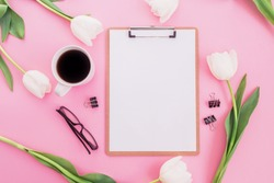 White tulips flowers with mug of coffee, clipboard and glasses on pink background. Blogger concept. Flat lay, top view.