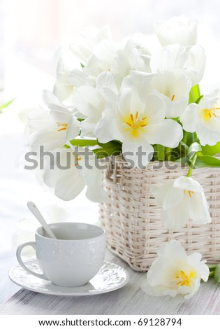 white tulips in a basket and cup of tea on the wooden table