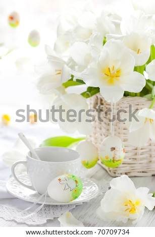 white tulips in a basket,easter eggs and cup of tea