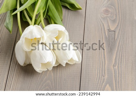 white tulips on rustic wood table, springtime flowers