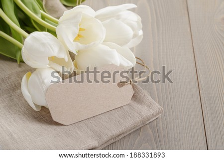white tulips on wood table with label or note