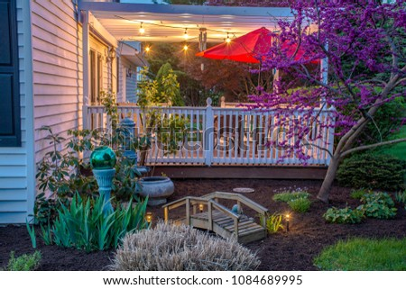white two story colonial home with finished deck bistro lights red umbrella red bud tree and finished landscaping #1084689995