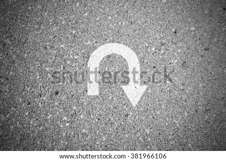 White u turn sign on asphalt concret street as background