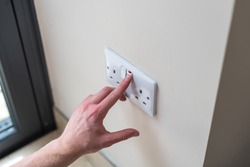 White Uk plug sockets being turned off to save electricity and money for the household