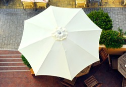 White umbrella seen from above on the terrace of a beach bar
