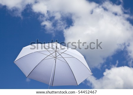 White umbrella under cloudy sky - stock photo