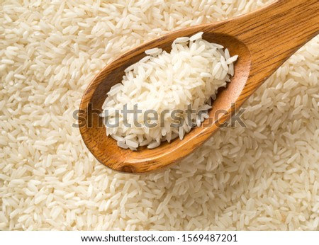 White uncooked, raw long grain rice full frame with wooden spoon top view flat lay from above - selective focus