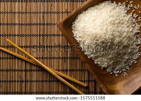 White uncooked, raw long grain rice in wooden bowl with chopsticks on bamboo mat with copy space top view flat lay from above - selective focus