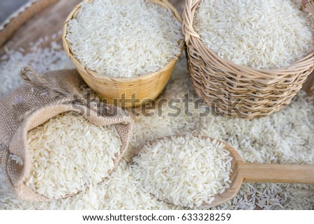 White uncooked rice on wooden surface.