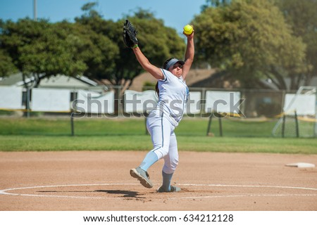 White uniform fast pitch softball pitcher winding up to throw in front view.
