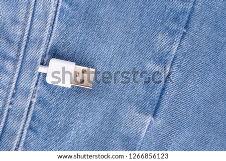 White USB cable in a denim pocket, USB cord with a denim pocket, the concept of communication and computer technology, social network #1266856123