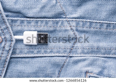 White USB cable in a denim pocket, USB cord with a denim pocket, the concept of communication and computer technology, social network #1266856126
