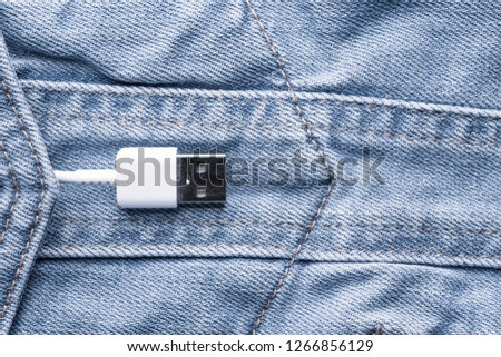 White USB cable in a denim pocket, USB cord with a denim pocket, the concept of communication and computer technology, social network #1266856129