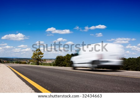 White van in a country road with some trees and a great blue sky above #32434663