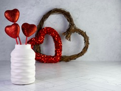 White vase filled with red glitter hearts sticking up with a red sparkly heart wreath and wooden heart wreath in the background on a herringbone tile counter.  Valentine's Day decor, love, be mine.