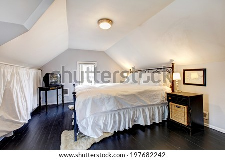 White velux bedroom with vaulted ceiling and old black hardwood floor. Furnished with iron frame bed, nightstand and tv