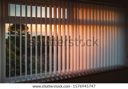 White vertical slat blinds hanging in front of a window as the sun is setting turning the light golden. The slats have sealed glued pockets and no cords at the bottom. Stock photo ©