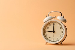 White vintage alarm clock on pastel orange paper background that show time at 9:00 o'clock with copy space.