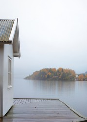 White vintage cabin  by the sea coast with wet pier . Foliage gold colors. Rainy , foggy day. Blurred background. Southern Norway