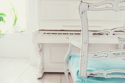 White vintage chair and piano in a white room