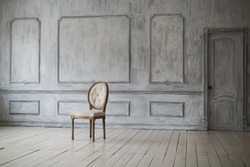 White vintage chair standing in front of a light wall with mouldings on wooden parquet floor.