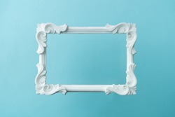 White vintage frame on pastel blue background. Minimal border composition.