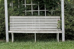White vintage wooden bench in the garden on the grass floor and background of vegetation and Victorian wooden ornaments.