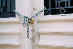 White vintage wooden door with black iron bar closed with chain and padlock.