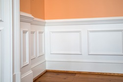 white wainscoting and chair rail on wall of orange peach dining living room of colorful home house