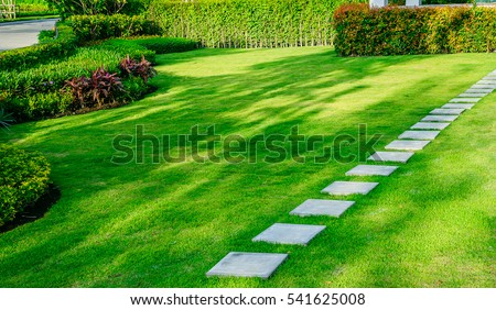 White walkway sheet in the garden, green grass with cement path  Contrasting with the bright green lawns and shrubs, shadows, trees, and morning sun Garden landscape design, lawn care service. Stock foto ©