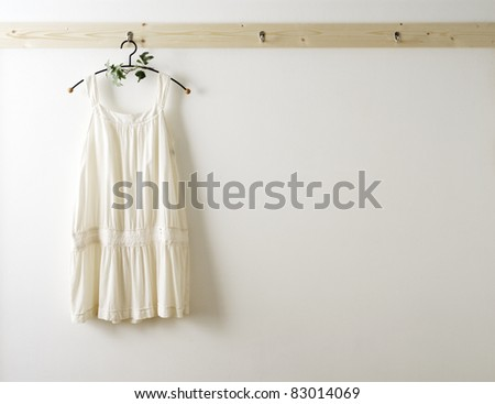 White wall and clothes on a hanger.