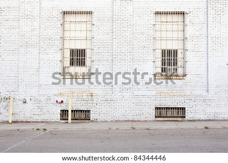 white wall background with barred windows and street
