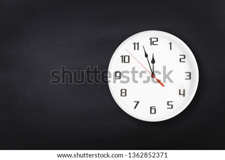 White wall clock on black chalkboard background. Five minutes to midnight. 5 min to 12 #1362852371