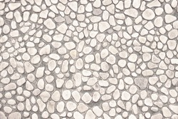 white wall of small stones, background light interior