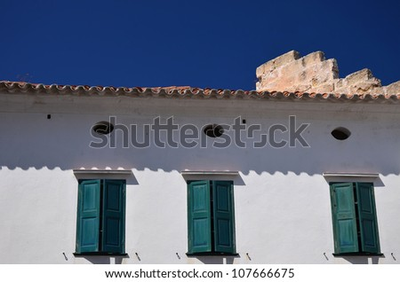 White wall of the house with a window with green shutters in a midday sun in old town of Mahon, Menorca, Balearic Islands, Spain