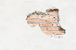 White wall which cracked until see the orange brick inside.