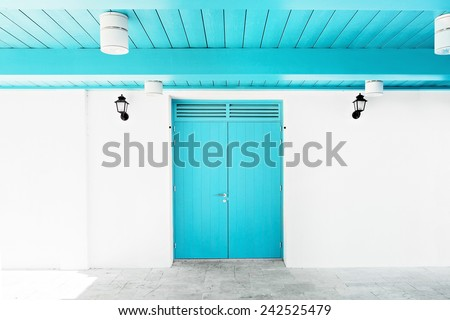 White wall with blue door and ceiling. Black lanterns at the entrance wall
