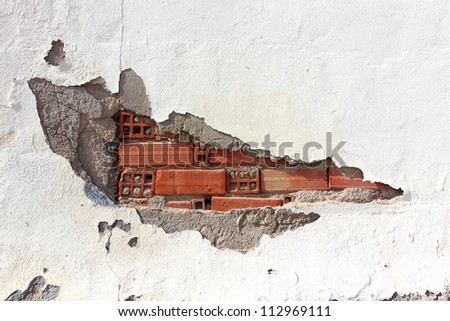 white wall with broken bricks and chipped being watched
