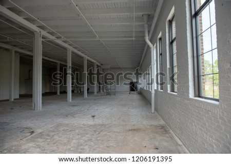 White walled abandoned warehouse under construction with white timber pillars, wooden ceilings and concrete floors #1206191395