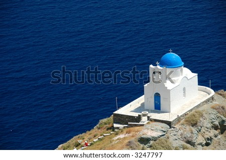 white wash cycladic chapel under the scorching Greek sun against the deepest blue sea