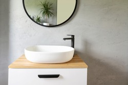 White washbasin with faucet on wooden countertop in minimalist modern bathroom. Scandinavian interior with stylish grey wall and round mirror. Copy space and nobody.
