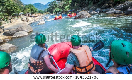 white water rafting with a team of green helmets in Thailand\n